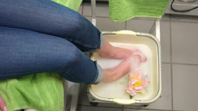 pedicure treatment at a beauty salon - soaking feet in a pedicure bowl - pedicure filmów i materiałów b-roll