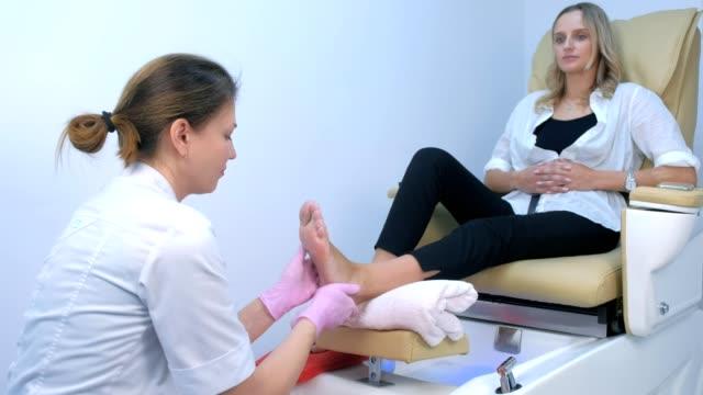pedicurist kobieta robi masaż stóp za pomocą kremu, kliniki zabiegu kosmetologii. - pedicure filmów i materiałów b-roll