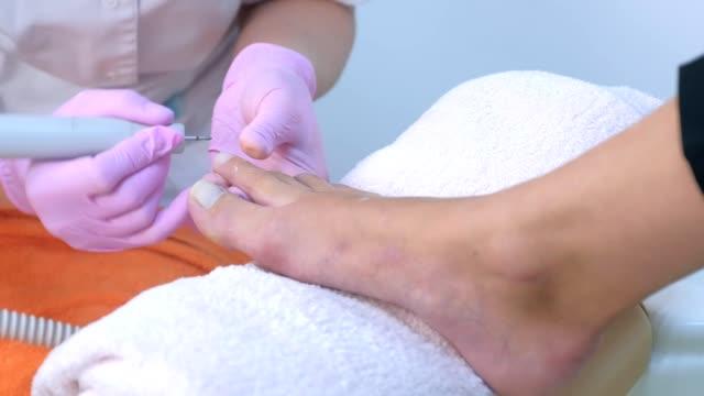 pedicurist kobieta usuwa byk z u cięć klienta za pomocą elektrycznej maszyny do paznokci. - pedicure filmów i materiałów b-roll