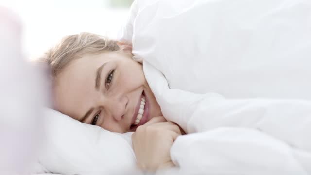 Peeking under duvet and smiling