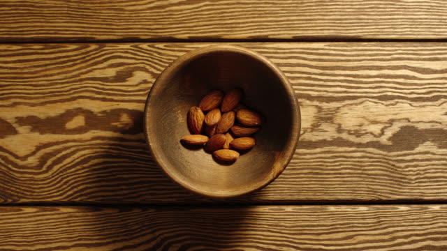 top view: peeled almonds appear in wooden cup and full this cup - stop motion - pugno video stock e b–roll