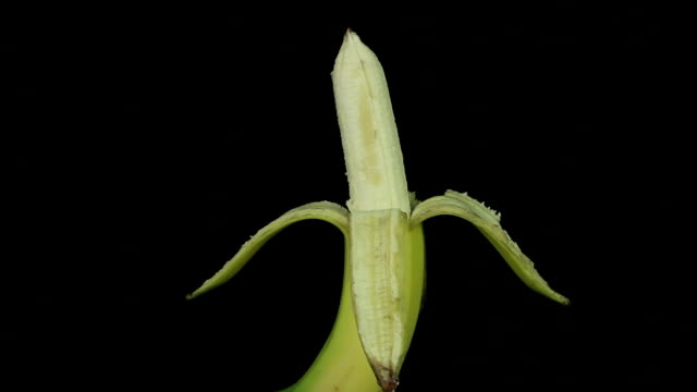 Peeled banana rotates on a black background loop video