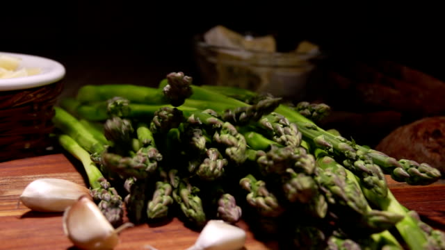 Peeled green asparagus falls onto a wooden board