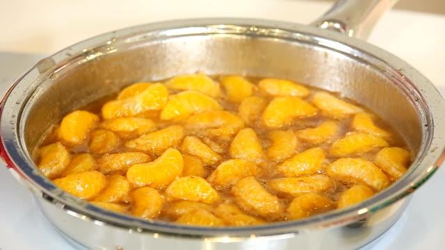 Peeled mandarin orange fillets with sugar in a pan video