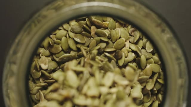 TOP VIEW: Peeled pumpkin seeds fall into glass jar - Slow Motion TOP VIEW: Peeled pumpkin seeds fall into glass jar - Slow Motion ingredient stock videos & royalty-free footage