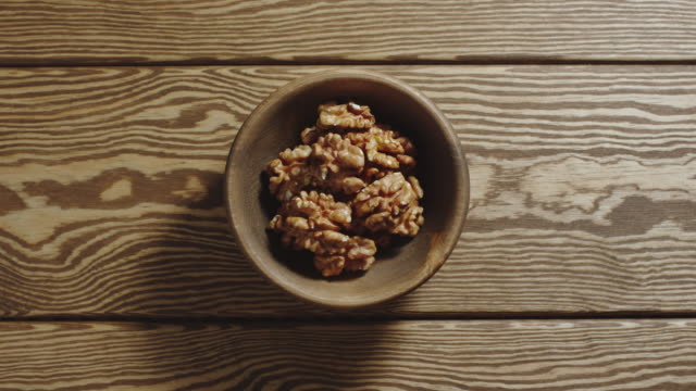 top view: peeled walnuts fill wooden cup. stop motion - pugno video stock e b–roll