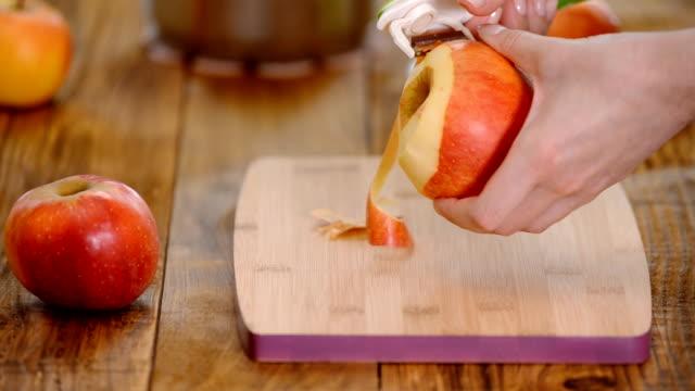 schälen sie einen großen, roten apfel für einen kuchen. - geschält stock-videos und b-roll-filmmaterial