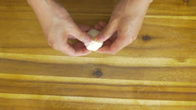 peeling garlic cloves on wooden cutting board