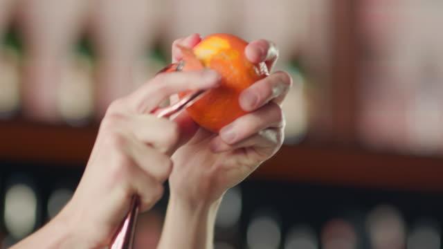 vídeos de stock, filmes e b-roll de descascar a laranja com um descascador - descascado