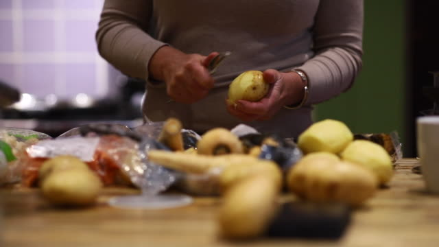 Peeling Potatoes A close-up shot of a woman peeling potatoes in preparation of a Christmas dinner. roast dinner stock videos & royalty-free footage