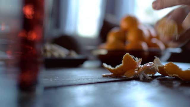 Peeling Tangerines on Wooden Table Close up of a young man peeling tangerines over a wooden table. Shot with shallow depth of field. peeled stock videos & royalty-free footage