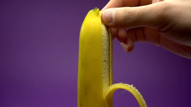 Peeling the skin from a banana. Violet background video