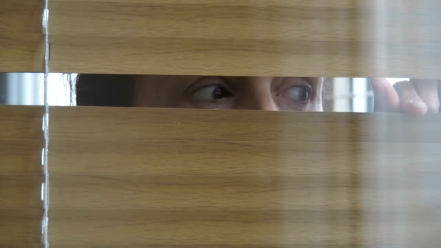 Peeps in the window. Peeps in the window. Eyes of a woman through the blinds. hiding stock videos & royalty-free footage