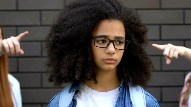 Peers pointing fingers at smart biracial girl, mocking nerd, verbal bullying