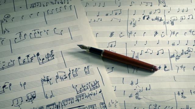 vidéos et rushes de stylo sur la main musique écrite de feuille - compositeur