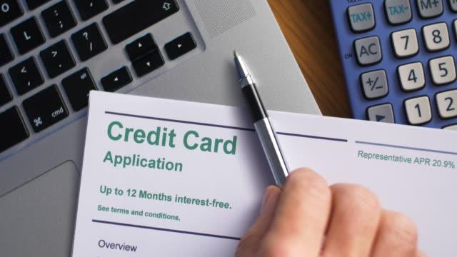 책상 위에 신용 카드 신청서가 놓인 펜. - 이율 스톡 비디오 및 b-롤 화면