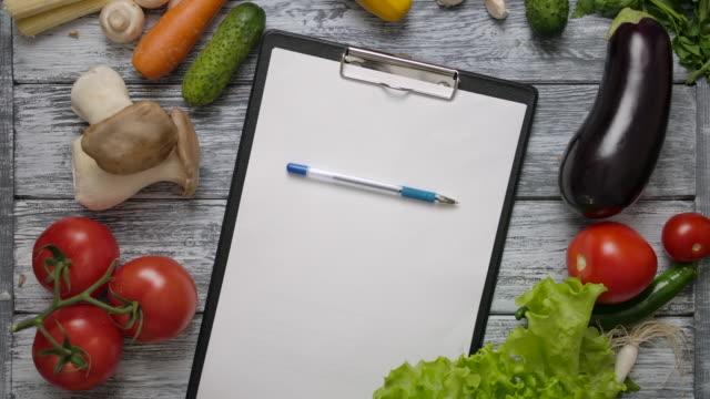 vídeos de stock e filmes b-roll de pen rolling on blank clipboard on kitchen table with vegetables - caneta