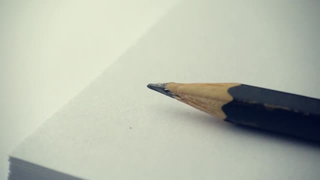 Pencil falling into white paper in slow motion
