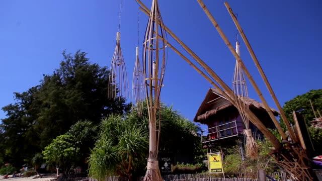 vídeos de stock, filmes e b-roll de penjor está balançando ao vento sobre o fundo de céu azul. penjor é o bastão de bambu decorativo. tailândia. - mobile