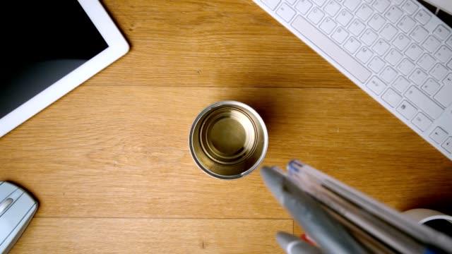 vidéos et rushes de stylos chute et atterrissant dans le bureau de verre - pots de bureau