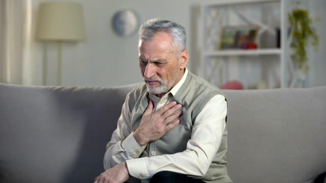 vídeos de stock e filmes b-roll de pensioner suffering chest pain, heart attack, problems with breathing, asthma - ataque cardíaco