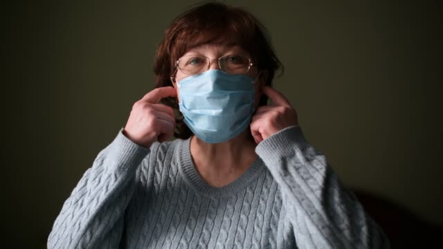 A pensioner takes off her medical mask and sighs with relief and a smile