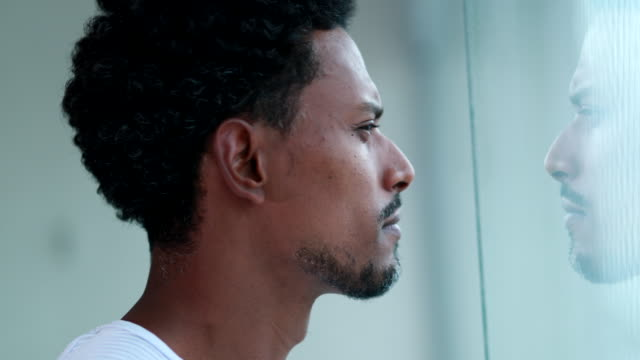 Pensive African man looking out window indoors. Thoughtful black person thinking deeply
