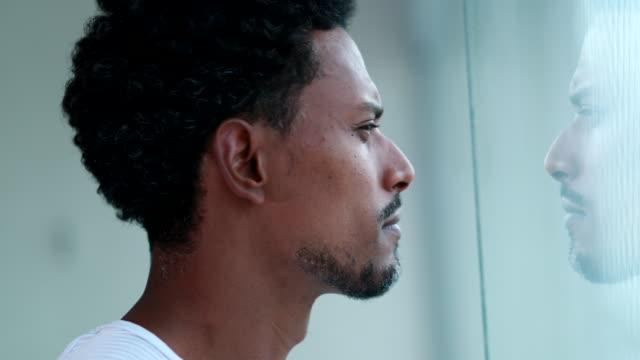 vídeos de stock, filmes e b-roll de homem africano pensativo olhando pela janela dentro de casa. pessoa negra pensativa pensando profundamente - contemplação
