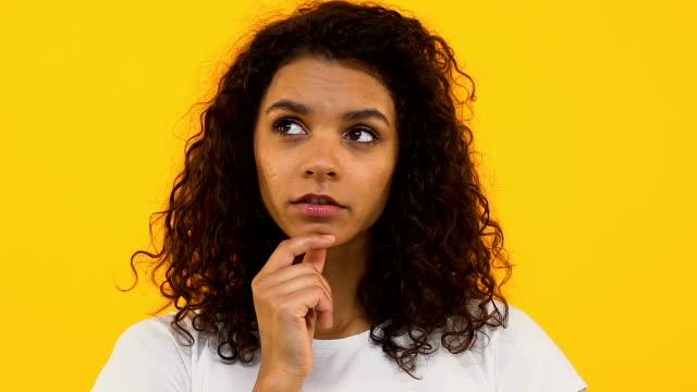 vídeos de stock, filmes e b-roll de mulher africana pensativa no fundo brilhante que pensa da escolha, sonhando a pessoa - perguntando