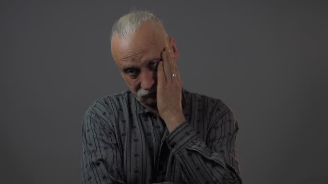 pensive and thoughtful elderly man stands with crossed arms - ludzka kończyna filmów i materiałów b-roll