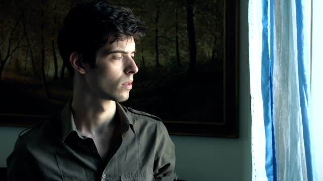 pensive and worried young man looking out the window - male eyes bildbanksvideor och videomaterial från bakom kulisserna