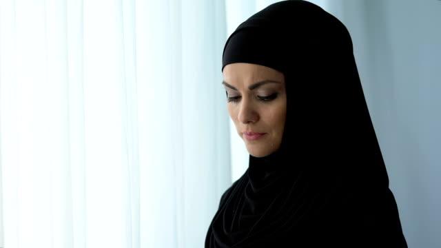 fundersam arabisk kvinna stående nära hem fönster, känna sig sårad, besvikelse - anständig klädsel bildbanksvideor och videomaterial från bakom kulisserna