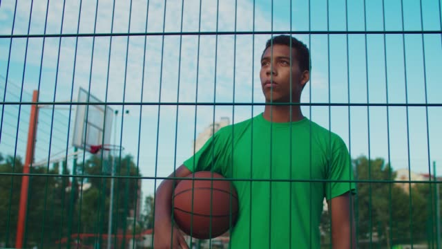 Pensive basketball player holding ball in urban court