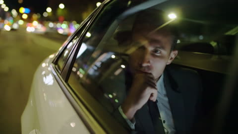 MS Pensive businessman on the back seat of a car Medium shot of a pensive businessman looking worried on the back seat of a limousine driving in the city at night. determination stock videos & royalty-free footage