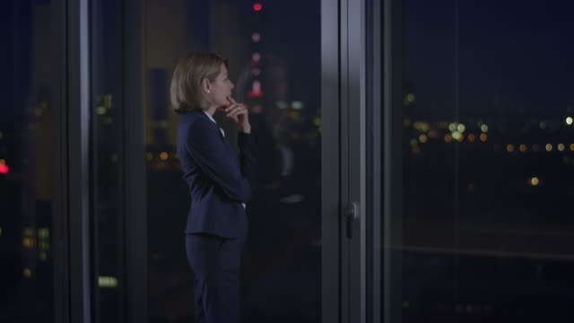 Pensive businesswoman standing in front of window video