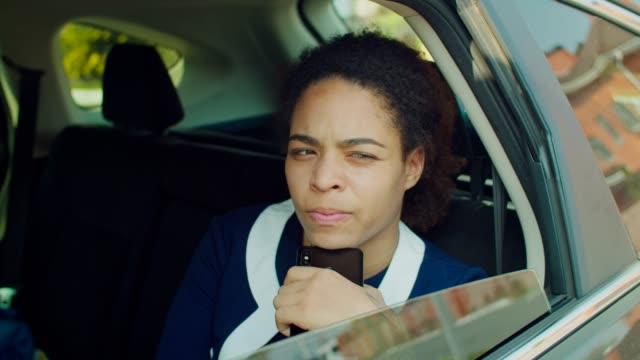 Pensive businesswoman with phone sitting in car backseat