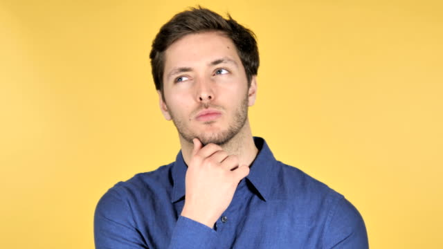 Pensive Casual Young Man Got New Idea on Yellow Background