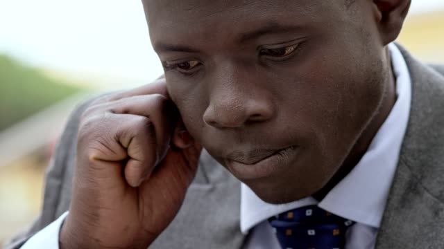 pensive day dreaming young african business man- close up video