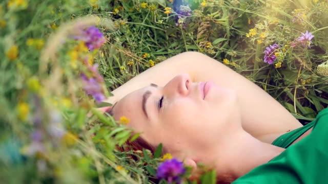 nachdenklich verträumt attraktive junge rothaarige Frau mit Blumen entspannende draußen auf einer Wiese voller Blumen. – Video