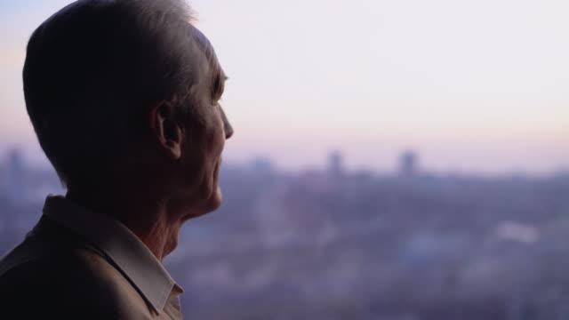 nachdenklicher älterer mann, der ins fenster schaut, einsamkeit im höheren alter, gesundheitliche probleme - introspektion stock-videos und b-roll-filmmaterial