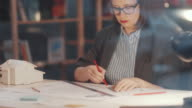 istock Pensive Female Architect Drawing Construction Plan at Desk in Office 1252336449