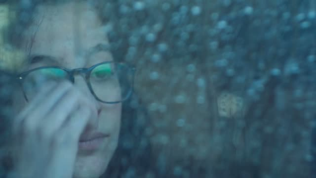 Pensive girl behind window in a rainy day. Shot in slowmotion video