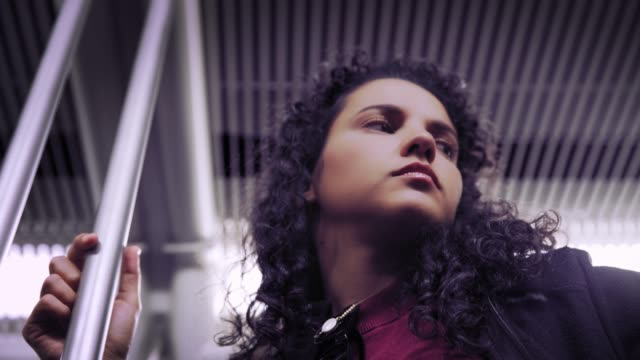 pensive hispanic young woman traveling in the train or subway - madrid video stock e b–roll