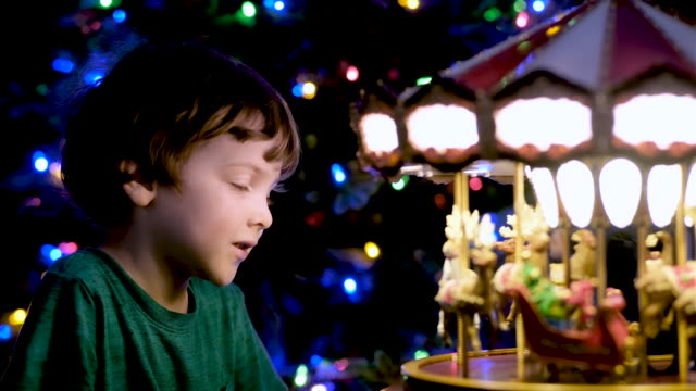 Pensive Little boy looking at a toy carrousel