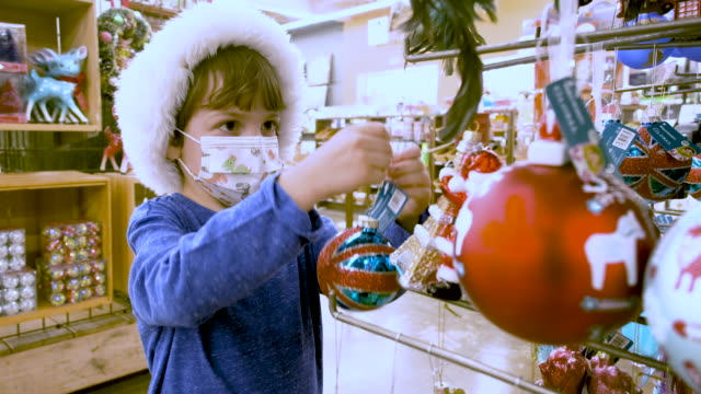 Pensive Little boy shopping for Christmas decorations wearing a Santa hat