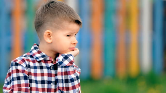 Pensive little boy sitting outside on a colourful background Pensive little boy sitting outside on a colourful background. autism stock videos & royalty-free footage