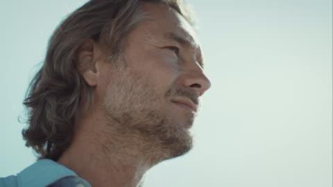pensoso uomo sulla spiaggia guardando in lontananza - guardare in una direzione video stock e b–roll
