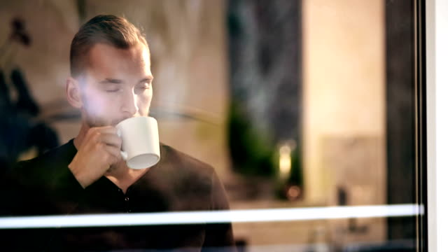 Pensive man looking out Lonely man wearing a black long sleeved shirt, standing in his home looking out of the window holding a coffee cup. Shot in 4K. handsome people stock videos & royalty-free footage