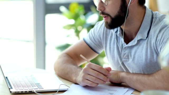 Pensive man with earphones attending online courses Smart education. Thoughtful man wearing glasses getting education while taking part in an online studying session while spending his time at home. online meeting stock videos & royalty-free footage