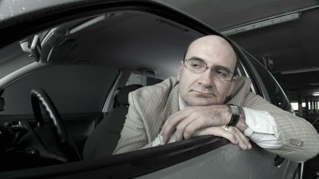 dolly hd: pensoso uomo di mezza età in un'auto - distrarre lo sguardo video stock e b–roll